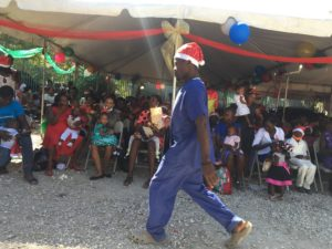 Christmas Party from Kay-O-Bois malnutrition program - Man walking with a santa hat on